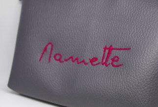 pochette en similicuir violet brodée avec l'écriture d'une personne